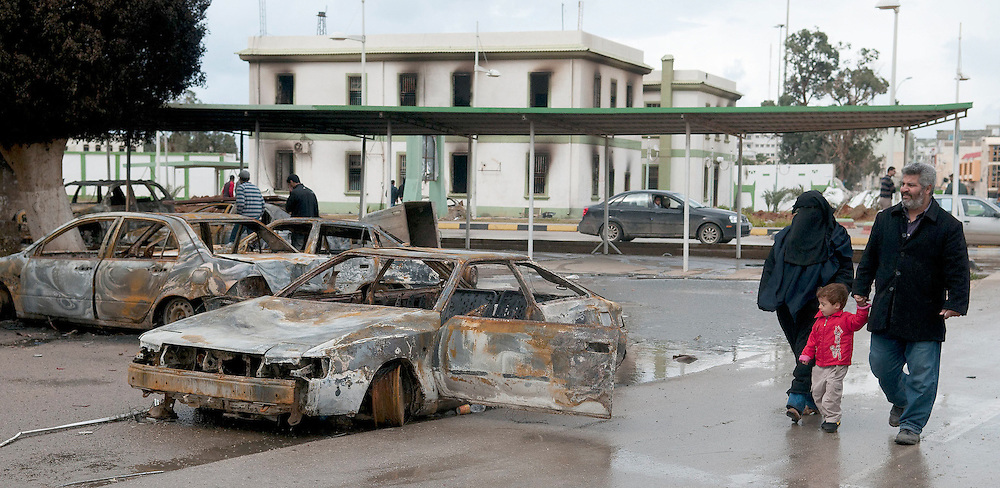 A family walks by burnt out cars in the army compound in Benghazi, Libya, during the country's 2011 Civil War.