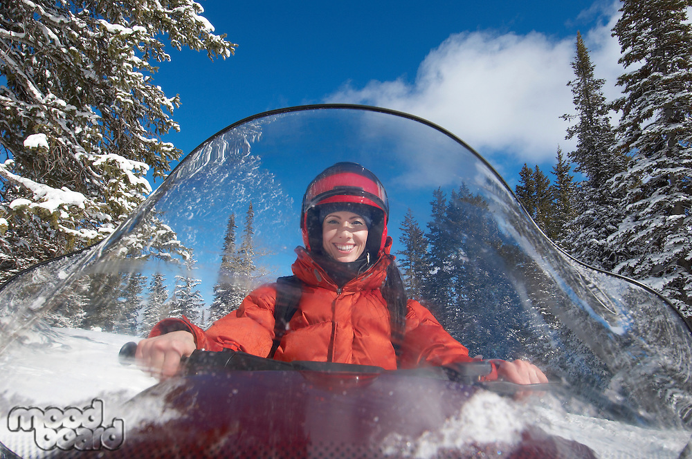 Smiling Woman Behind Windshield of Snowmobile