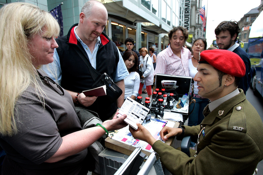 GERMANY - BERLIN - Tourists having their passports stamped by a fake soldier at Checkpoint Charlie. PHOTO GERRIT DE HEUS