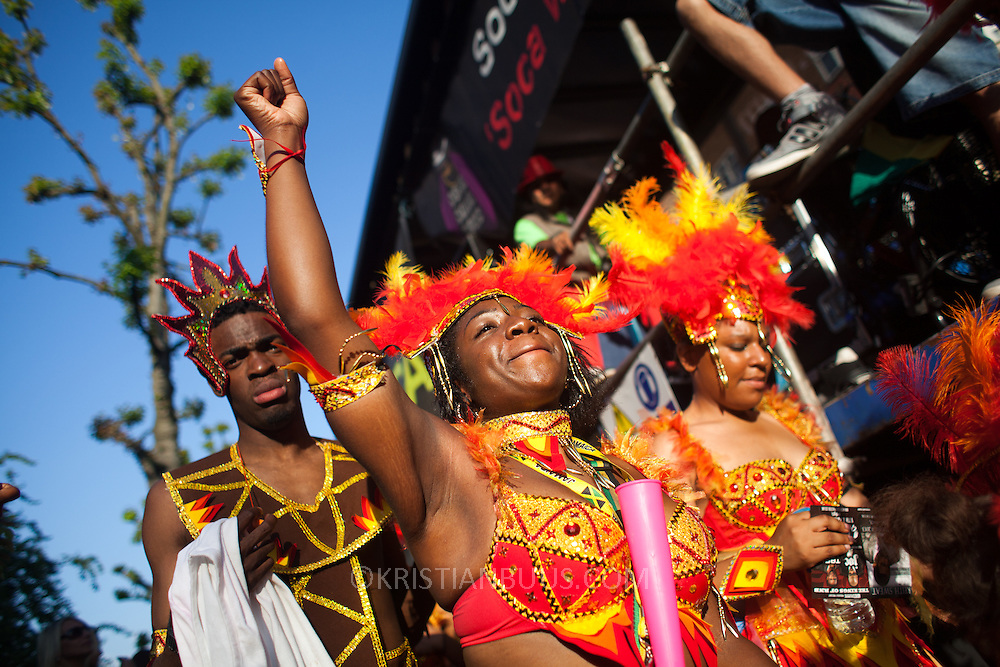 Dancers in costumes enjoy the music and the sun. The Notting Hill Carnival has been running since 1966 and is every year attended by up to a million people. The carnival is a mix of amazing dance parades and street parties with a distinct Caribbean feel.