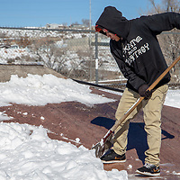 Sonnie Sam, 13, shovels snow at the new skate park in Gallup Thursday so he can get back to skating soon.