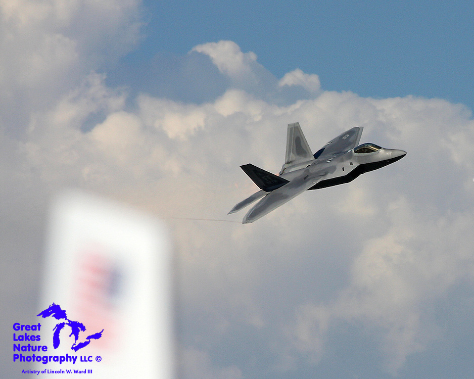 A photographer gets lucky, every now and then. In this shot, a US Air Force F-22 Raptor is coming by me at nearly 500 mph. As I followed the aircraft using my camera's motor drive, I just happened to pan over the tail of another aircraft, with the US flag defocused but clearly evident. The huge thunderstorm in the background adds to the overall effect of the image.