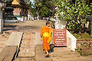 11 MARCH 2013 - LUANG PRABANG, LAOS:   A Buddhist novice walks into Wat Xieng Thong, the most historic Buddhist temple in Luang Prabang.  PHOTO BY JACK KURTZ