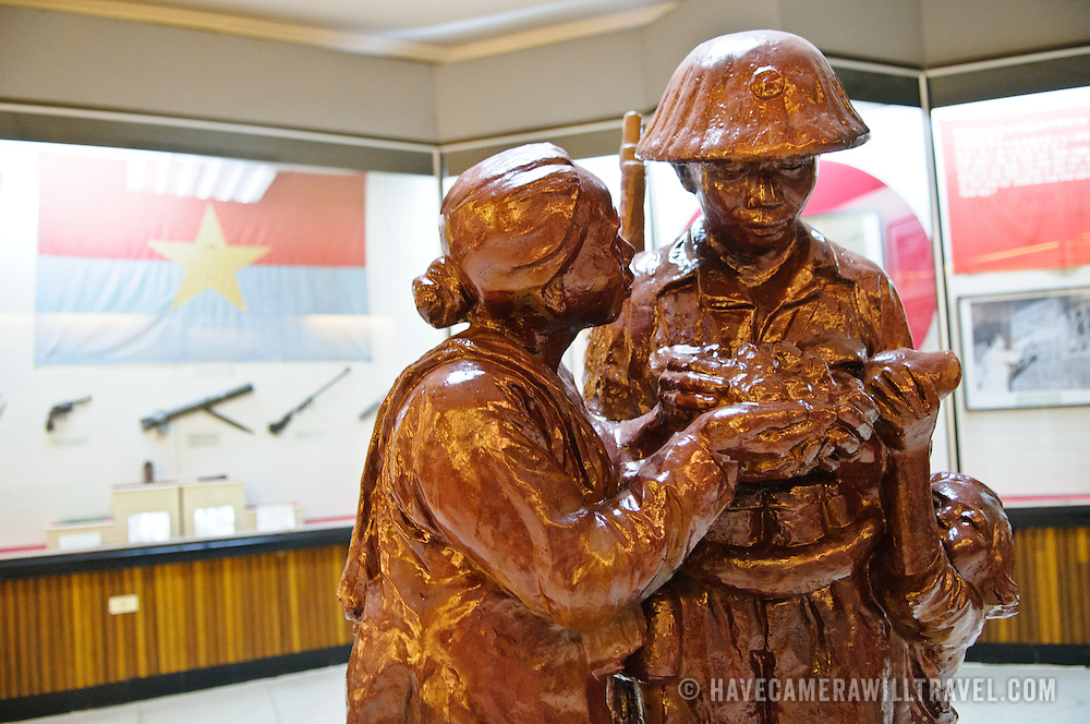 A statue in the foreground, with a revolutionary flag and guns in the exhibit case in the background at left. The Museum of the Vietnamese Revolution in the Tong Dan area of Hanoi, not far from Hoan Kiem Lake, was established in 1959 and is devoted to the history of the socialist revolutionary movement in Vietnam.