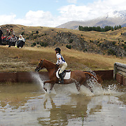 Zoe McNeilly riding Strictly Kosha in action at the water jump during the Cross Country event at the Wakatipu One Day Horse Trials at the Pony Club grounds,  Queenstown, Otago, New Zealand. 15th January 2012. Photo Tim Clayton