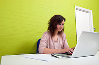 Close-up view of Young woman working at her desk