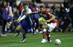 Wigan Athletic's Josh Windass (left) and Bristol City's Nathan Baker (right) battle for the ball during the Sky Bet Championship match at the DW Stadium, Wigan.