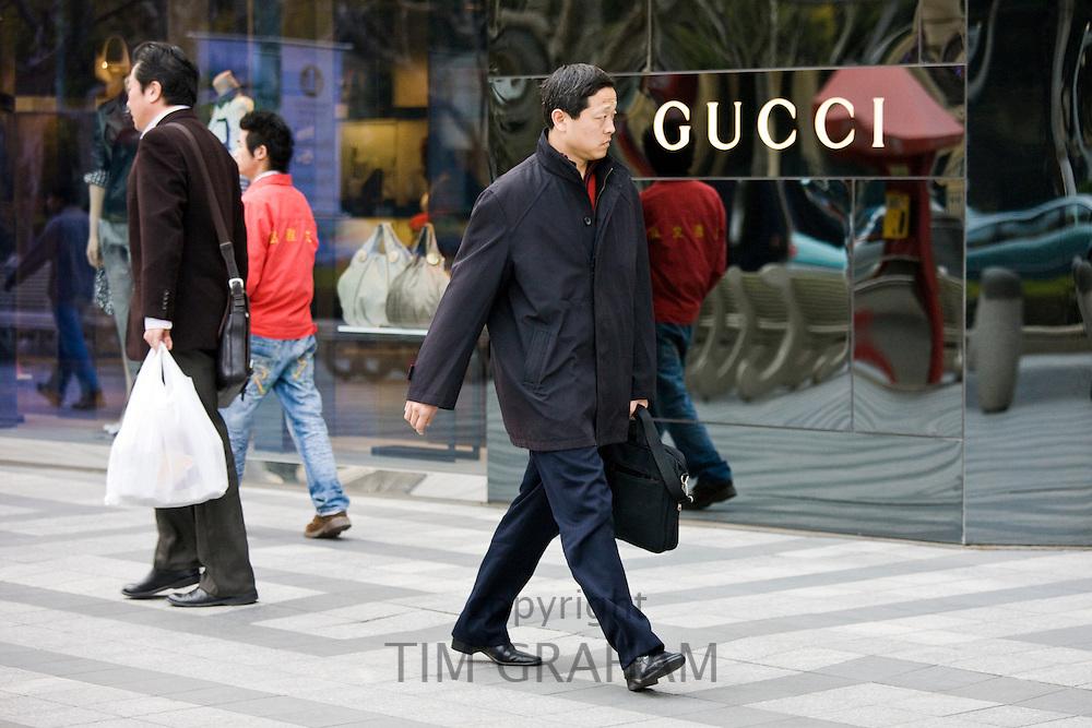 Man walks past Gucci shop on Nanjing Road, central Shanghai, China