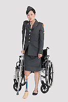 Disabled female US military officer with crutch standing in front of wheelchair over gray background