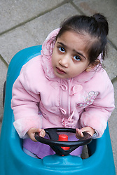 Little girl riding in a toy car looking puzzled,