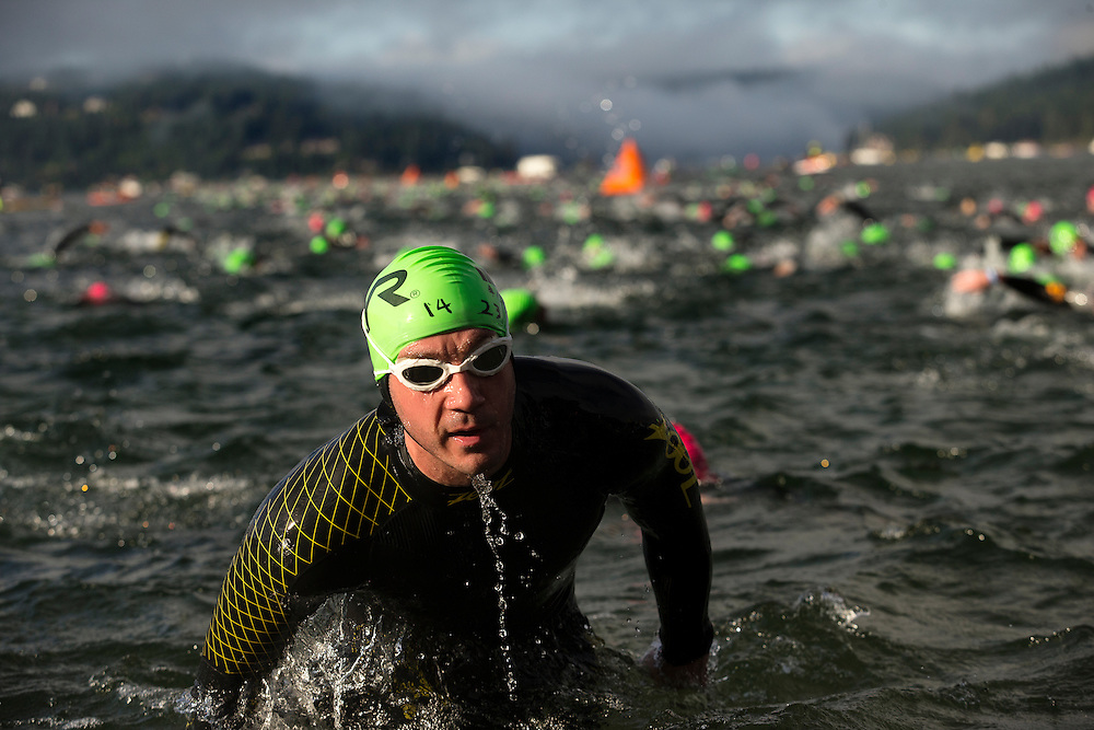 GABE GREEN/Press<br /> <br /> Neil Amadio emerges from lake Coeur D'alene after his first lap of the swim portion of Ironman Coeur d'Alene early Sunday morning.