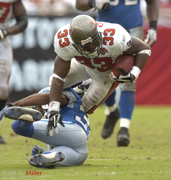 Oct. 5, 2005; Tampa, FL, USA;  Tampa Bay Buccaneers running back #33 Earnest Graham goes airborne after being tripped up by Detroit Lions defender R.W. McQuarters during the second half of the Bucs 17-13 win at Raymond James Stadium.          ©2005 Scott A. Miller..©2005 Scott A. Miller