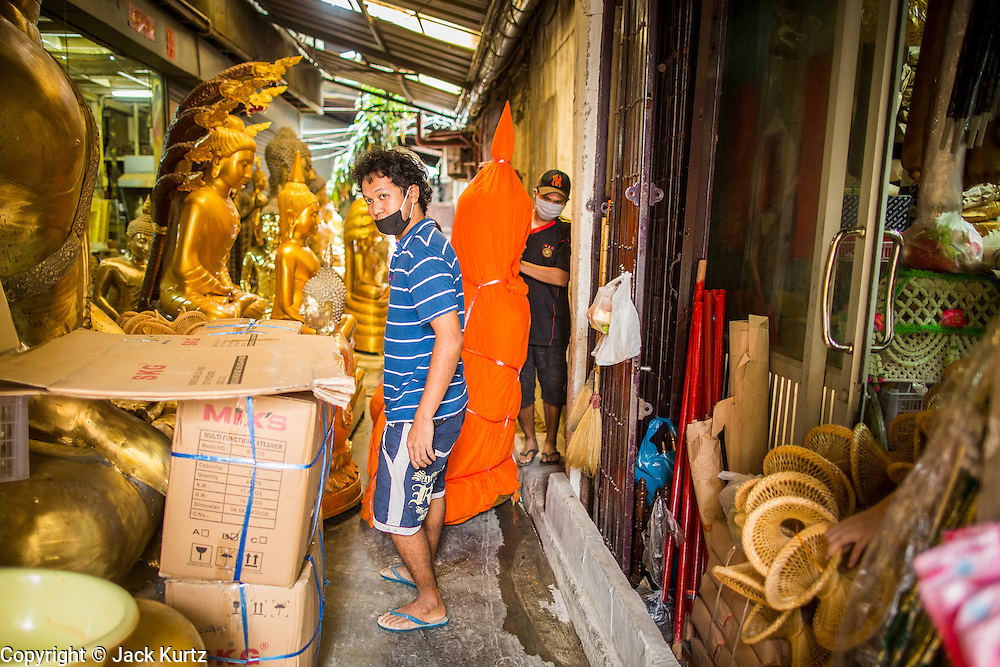 "12 NOVEMBER 2012 - BANGKOK, THAILAND:   Men bring a sold statue of the Buddha out to a waiting delivery truck on Bamrung Muang Street in Bangkok. Buddhas are covered in saffron when they are moved. Thanon Bamrung Muang (Thanon is Thai for Road or Street) is Bangkok's ""Street of Many Buddhas."" Like many ancient cities, Bangkok was once a city of artisan's neighborhoods and Bamrung Muang Road, near Bangkok's present day city hall, was once the street where all the country's Buddha statues were made. Now they made in factories on the edge of Bangkok, but Bamrung Muang Road is still where the statues are sold. Once an elephant trail, it was one of the first streets paved in Bangkok. It is the largest center of Buddhist supplies in Thailand. Not just statues but also monk's robes, candles, alms bowls, and pre-configured alms baskets are for sale along both sides of the street.    PHOTO BY JACK KURTZ"