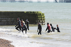 © Licensed to London News Pictures. 25/03/2017. Brighton, UK. Members of the Brighton surf life saving club, RNLI, Coastguard and the police supported by boats and the coastguard helicopter search for a man that went missing while swimming in the sea in Brighton. Photo credit: Hugo Michiels/LNP