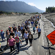 Hundreds of Oso, Darrington and Arlington residents walk on State Route 530 before the highway was reopened to cars. A little more than two months after the Oso mudslide destroyed a neighborhood and killed 43 people, the highway through the heart of the slide reopened to vehicle traffic. Motorists must follow a pilot car that directs a single direction at a time. Photographed on Saturday, May 31, 2014.