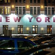 NLD/Rotterdam/20180412 - Gevel aan de buitenzijde met de woorden Hotel New York in de avond