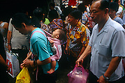A Macanese mother carries her baby in a sling on her back while shopping for supplies in a Macau market, China.