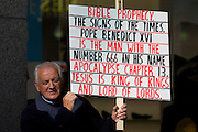 A protester stands outside Westminster Cathedral during Pope Benedict XVI's papal tour of Britain 2010. Voicing opposition to Catholic thinking the man has hand-written a sign of Biblical prophecies stating that the Pope is the Anti-Christ, with the Devil's number 666 in his name. This is during Pope Benedict 's papal tour of Britain 2010, the first visit by a pontiff since 1982. Taxpayers footed the £10m bill for non-religious elements, which largely angered a nation still reeling from the financial crisis. Pope Benedict XVI is the head of the biggest Christian denomination in the world, some one billion Roman Catholics, or one in six people. In Britain there are about five million Catholics but only a quarter of Catholics regularly attend Sunday Mass and some churches have closed owing to spending cuts.