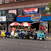 Gathering of scooter enthusiasts at Callaloo Caribbean Kitchen bar and grill on State Street in Bellingham, Washington