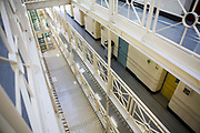 Looking down from the top floor (4th) at the central walkway and suicide nets of Benbow wing inside HMP/YOI Portland, a resettlement prison with a capacity for 530 prisoners. Dorset, United Kingdom.