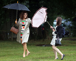 Not so Glorious Goodwood… Two race goer's  get caught up in the rain and wind as they arrive for  the opening day of Glorious Goodwood in the UK, Tuesday, 30th July 2013 <br /> Picture by Stephen Lock / i-Images