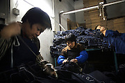 "Workers sew jeans using a sanding machine in Mr Huang's factory in Zhongshan city, China, while a child sleeps on a pile of jeans. .This picture is part of a photo and text story on blue jeans production in China by Justin Jin. .China, the ""factory of the world"", is now also the major producer for blue jeans. To meet production demand, thousands of workers sweat through the night scrubbing, spraying and tearing trousers to create their rugged look. .At dawn, workers bundle the garment off to another factory for packaging and shipping around the world..The workers are among the 200 million migrant labourers criss-crossing China.looking for a better life, at the same time building their country into a.mighty industrial power."