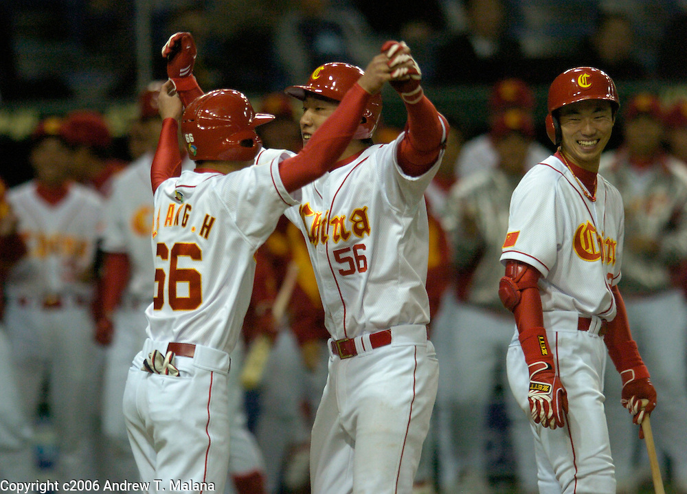 Team China catcher Wei Wang #56 is congratulated by#66 Hong Bo Zhang after Wang hit a two-run home in the 4th inning off of Team Japan's Koji Uehara. This is the first home run of the World Baseball Classic at Tokyo Dome, Tokyo, Japan.