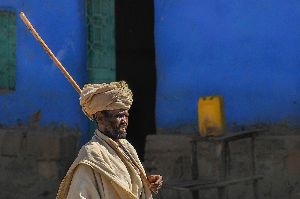 Shepherd walking with a stick in front of a blue wall on the streets of Debark, Ethiopia