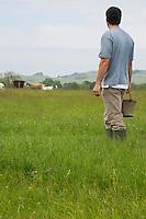 Man holding bucket in field rear view