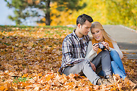 Couple looking at pictures on digital camera in park during autumn