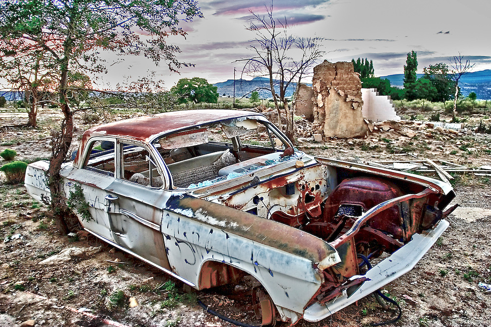 trashed out car and remnants of an adobe house in Cubero, New Mexico