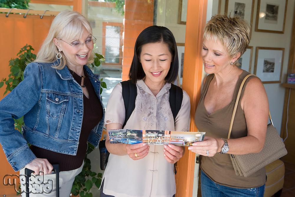 Three women holding ticket on vacation