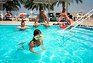 A child wearing oversize gogles swims as other Israelis enjoy the summer sun at the En Gedi Spa next to the Israeli Dead Sea Saturday Aug. 4, 2001. Despite the 11 months of violence Israelis and Palestinians take a break to enjoy the mediterrenean beaches and the Dead Sea, where under growing tensions and in the case of Gaza under closure people try to  make the best of their summer and carry on a normal life.
