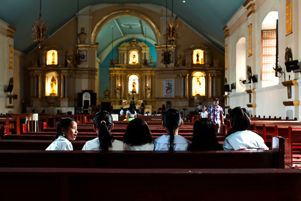 Schoolgirls chatter quietly in church, in Laoag, Philippines. Copyright 2015 Reid McNally.