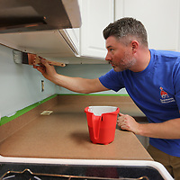 Brit Harris, a SHerwin Williams employee from the Mall store in Tupelo, trims out under the cabinets inside the kitchen of the Family Resource Center in Tupelo Tuesday norning.