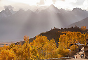 Rays of afternoon light illuminate a row of chortens (stupas) and autumn trees in the village of Karsha in the Zanskar Valley, Ladakh India.