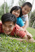 Father with son and daughter (7-9) lying in grass in park