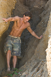 Good looking Shirtless fit man  climbing down a rock face out in Montauk, NY
