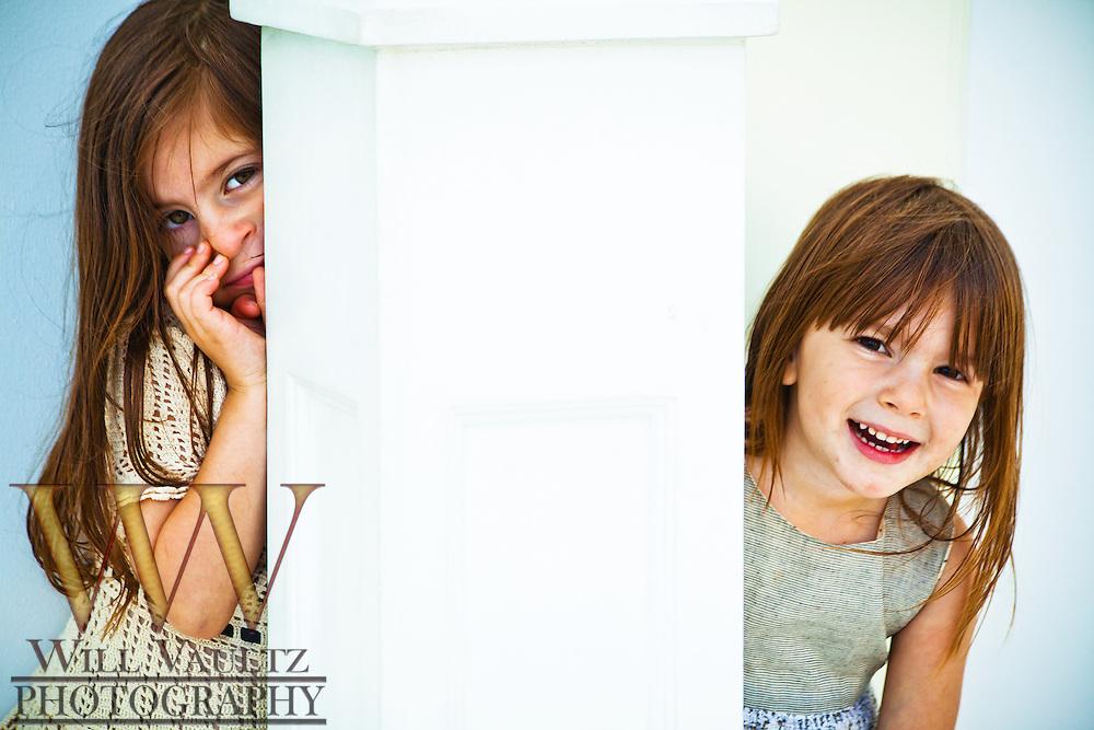 Girls hiding behind column