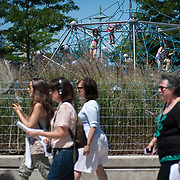 """June 21, 2014 - New York, NY : <br /> The city was flooded with music on Saturday as Make Music New York brought more than 1,300 free concerts to the city's streets and parks. The annual festival's program included """"And Death Shall Have No Dominion,"""" a piece by composer Pete M. Wyer, honoring the centenary of the birth of the poet Dylan Thomas. The piece -- a participatory singing event -- was performed by a synchronized headphone choir. The choir's singers began in smaller groups around lower Manhattan and culminated in a meeting in Battery Park City. Children spy the group of sopranos from a playground along the Hudson River Greenway.  CREDIT: Karsten Moran for The New York Times"""