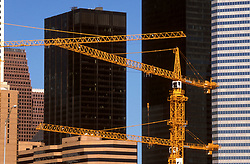 Stock photo of heavy construction cranes appearing against the downtown Houston skyline.