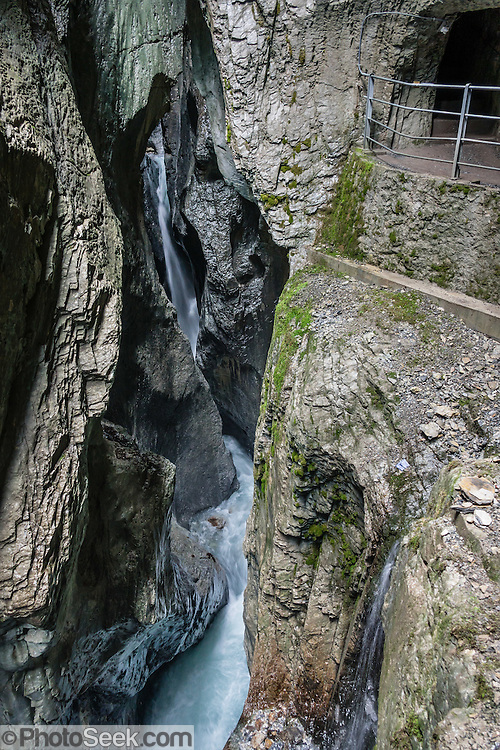 Walk a narrow walkway carved through Rosenlaui Glacier Gorge / Gletscherschlucht, near Meiringen, Switzerland, the Alps, Europe. In this deep ravine, the Weissenbach River has eroded potholes into a natural cathedral of slate and limestone.