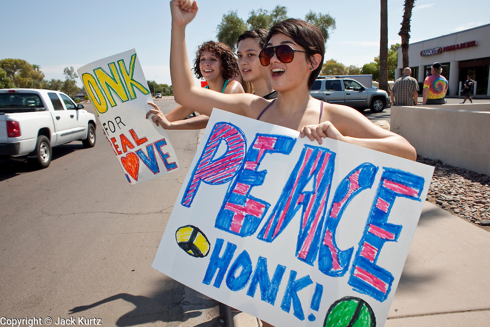 "Sept. 6, 2009 -- TEMPE, AZ: GABRIELLA MARVIN, from Phoenix, AZ, and her friends picket and encourage motorists to honk in front of the Faithful Word Baptist Church in Tempe, AZ, Sunday. Steven Anderson, the minister at the Faithful Word Baptist Church, an independent fundamentalist Baptist church, in Tempe has repeatedly said he hoped US President Barack Obama would die from a brain tumor and Sunday, Sept. 6, reiterated that he ""hates"" President Obama. More than 200 people from a variety of liberal and progressive churches in the Phoenix area picketed Anderson's church Sunday morning, outnumbering his small congregation of about 50.  Photo by Jack Kurtz"
