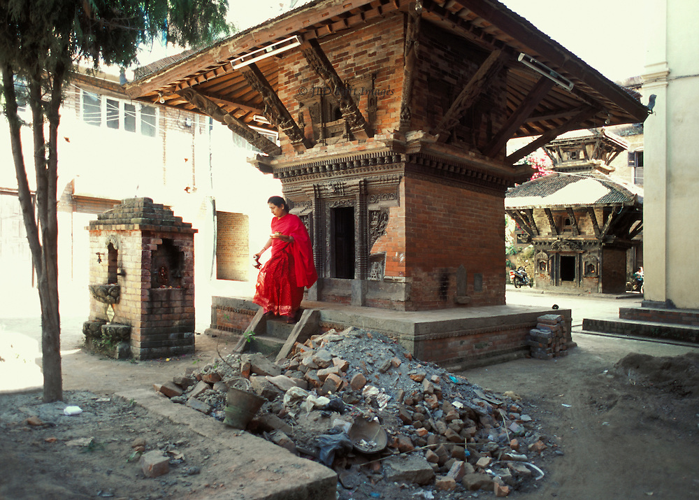 Hindu shrine newly built in Kathmandu street.  Woman in red sari emerges after making an offering to the deity within. Building rubble piled in front, not having been removed.  A second shrine of similar type can be seen down the street  Both are very small; a home for the figure of the deity inside.