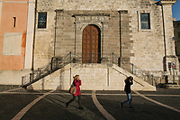 "SUTERA, ITALY - 8 JANUARY 2018: Residents walk by the church in the historical center of Sutera, Italy, on January 8th 2018.<br /> <br /> Sutera is an ancient town plastered onto the side of an enormous monolithic rock, topped with a convent, in the middle of the western half of Sicily, about 90 minutes by car south of the Sicilian capital Palermo<br /> Its population fell from 5,000 in 1970 to 1,500 today. In the past 3 years its population has surged  after the local mayor agreed to take in some of the thousands of migrants that have made the dangerous journey from Africa to the Sicily.<br /> <br /> ""Sutera was disappearing,"" says mayor Giuseppe Grizzanti. ""Italians, bound for Germany or England, packed up and left their homes empty. The deaths of inhabitants greatly outnumbered births. Now, thanks to the refugees, we have a chance to revive the city.""<br />  Through an Italian state-funded project called SPRAR (Protection System for Refugees and Asylum Seekers), which in turn is co-funded by the European Union's Fund for the Integration of non-EU Immigrants, Sutera was given financial and resettlement assistance that was co-ordinated by a local non-profit organization called Girasoli (Sunflowers). Girasoli organizes everything from housing and medical care to Italian lessons and psychological counselling for the new settlers.<br /> The school appears to have been the biggest beneficiary of the refugees' arrival, which was kept open thanks to the migrants.<br /> Nunzio Vittarello, the coordinator of the E.U. project working for the NGO ""I Girasoli"" says that there are 50 families in Sutera at the moment."