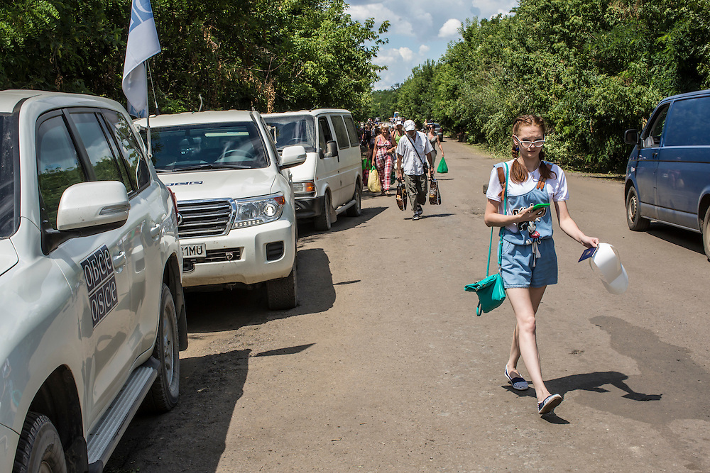 ZAITSEVE, UKRAINE - JULY 9, 2016: Civilians walk from Ukrainian government-controlled territory past OSCE vehicles at a checkpoint toward the rebel-held Donestk People's Republic in Zaitseve, Ukraine. The mission tracks violations of the Minsk-II ceasefire agreement, among other tasks. CREDIT: Brendan Hoffman for The New York Times