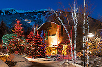 Whistler Village glows with colored lights on a snowy winter evening, and the mountain rises steeply behind.