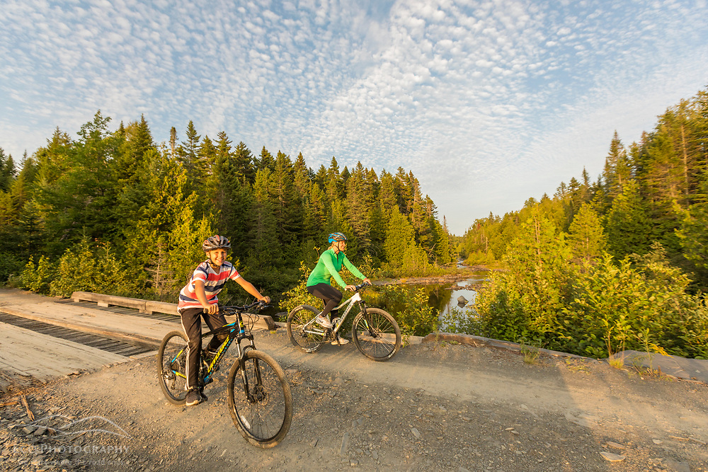 A woman and her son ride bikes near Pushineer Pond in Aroostook County, Maine. Deboullie Public Reserve Land.