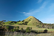 grass covered volcanic cone amidst a rural waikato landscape against the blue sky background, at waitetuna, waikato, new zealand