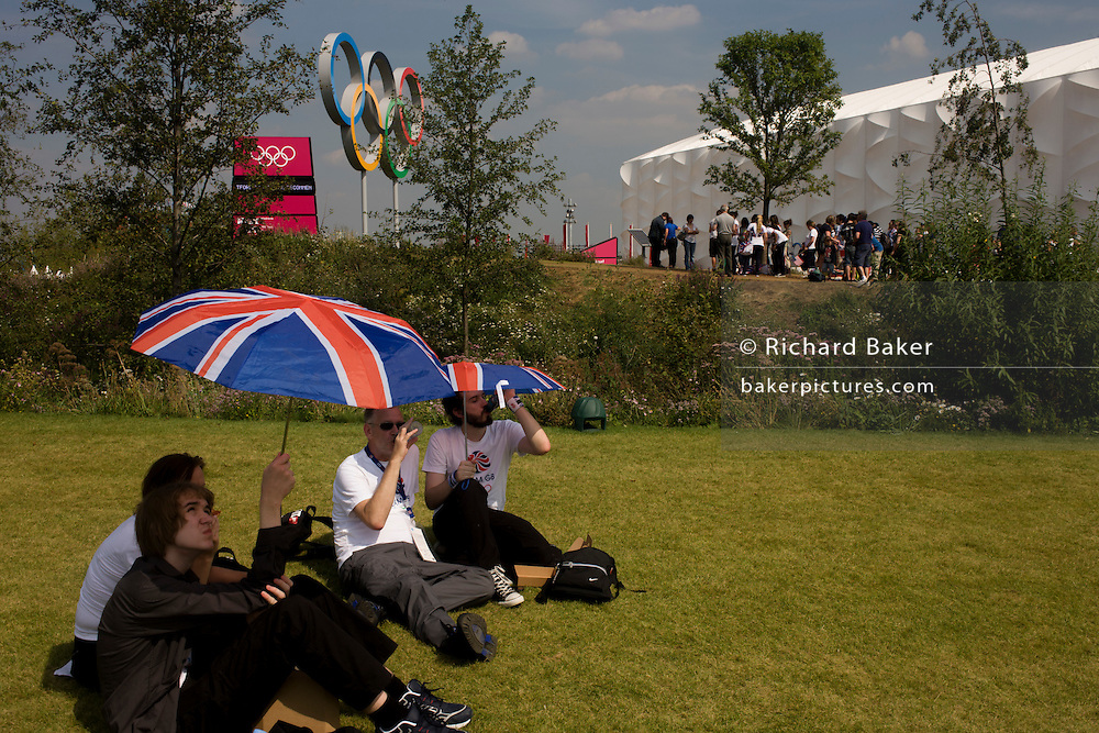 Brits enjoy a hot summer to watch live coverage from a large tv screen in the Olympic Park during the London 2012 Olympics. Under union jack umbrellas they sit on green grass located on a hilltop across from giant Olympic rings used as a background for spectators' photos. London's Olympic Park, at just under a square mile, is the largest new park in the city for more than 100 years. The planting of 4,000 trees, 300,000 wetland plants and more than 150,000 perennial plants plus  nectar-rich wildflower make for a colourful setting for the Games. This land was transformed to become a 2.5 Sq Km sporting complex, once industrial businesses and now the venue of eight venues including the main arena, Aquatics Centre and Velodrome plus the athletes' Olympic Village. After the Olympics, the park is to be known as Queen Elizabeth Olympic Park.